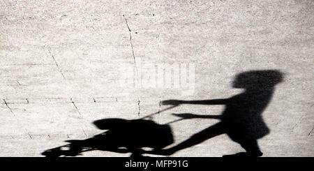 Ombre silhouette d'une jeune femme en poussant une poussette sur les trottoirs de la ville en noir et blanc Banque D'Images