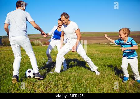 Famille heureuse de jouer avec une balle sur la nature au printemps, l'été. Banque D'Images