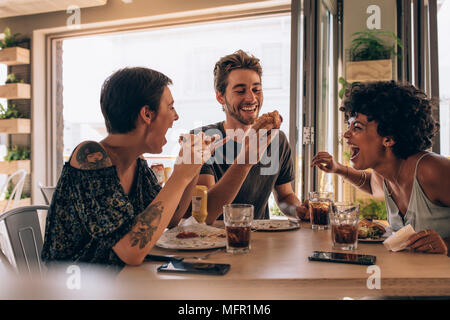 Groupe d'amis ayant burger du restaurant. Cheerful young people eating hamburger et bénéficiant à un fast-food. Banque D'Images