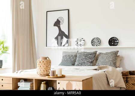 Oreillers noir et blanc à motifs africains, des plaques et de l'affiche dans un intérieur chambre à coucher ethnique Banque D'Images