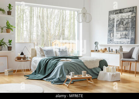 4f9c2d17df27e7 ... Peinture au-dessus de l armoire blanche près de lit avec literie pastel  vert