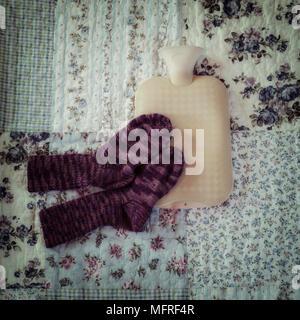 Bouteille à eau chaude avec des chaussettes tricotées main sur un lit vintag Banque D'Images