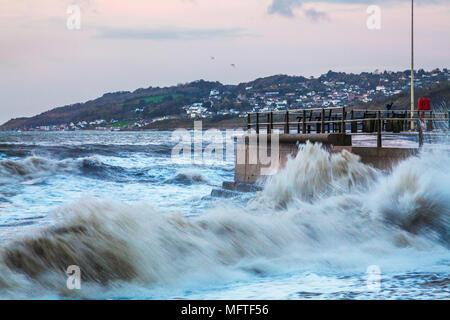 Les vagues se briser contre le quai à Charmouth dans le Dorset au lever du soleil. Banque D'Images