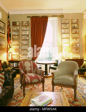 Salon traditionnel avec des draperies rouge tapis oriental fauteuils tables en bois et une collection de produits les boîtes d'ombre. Banque D'Images