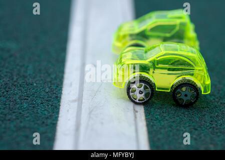 Voitures jouets en plastique transparent vert sur la ligne de départ Banque D'Images