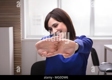 Close-up of a young woman Stretching Her Hands in Office Banque D'Images