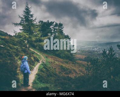 Ilkley Moor, West Yorkshire, Royaume-Uni. 27 avril 2018. Météo France: Ilkley Moor, West Yorkshire, Royaume-Uni. 27 avril 2018. De fortes pluies pendant une bonne partie de la journée a donné les conditions atmosphériques sur Ilkley Moor. Ici une femelle walker en totalité l'imperméable bénéficie d'une vue sur les moody Ilkley. Credit: Rebecca Cole/Alamy Live News Banque D'Images