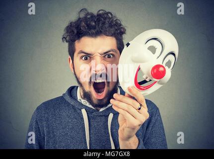 Portrait jeune homme qui crie en colère colère tenant un masque de clown isolé sur fond de mur gris. Les émotions humaines sentiments Banque D'Images