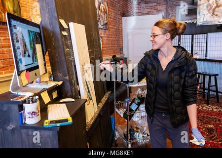 Artiste Katie Maher faisant référence à une image d'ordinateur lors de la création d'une peinture à l'huile dans sa galerie; Salida, Colorado, USA Banque D'Images