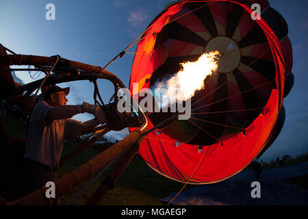 Ravi hot air balloon pilot chauffage son ballon pour une soirée de l'activité des bougies de chauffage Banque D'Images