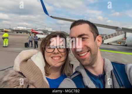 Couple heureux en tenant avec selfies smartphone ou appareil photo en extérieur, près de l'aéroport avion. Banque D'Images