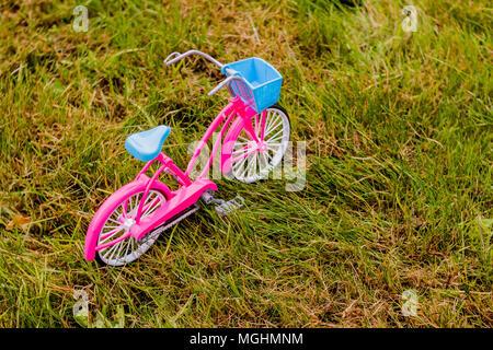 Petit, élégant, décoratif, rose, femme vélo. Les jouets pour enfants. Location jouet pour poupées. Un vélo pour enfant en rose. Un vélo rose avec des roues de formation. modèle de vélo sur l'herbe. Sport Concept Vie Active Banque D'Images