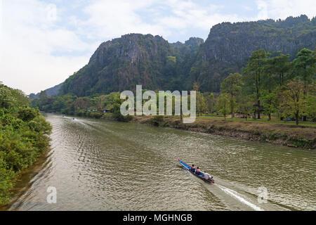 Avis de trois petits bateaux sur la rivière Nam Song et les montagnes karstiques de calcaire près du Tham Chang (ou Jang ou Jung) Grotte à Vang Vieng, Laos. Banque D'Images