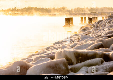 Les bollards silhouetté dans misty,mer gelée,Hernesaarenranta,Helsinki,Finlande,Europe Banque D'Images