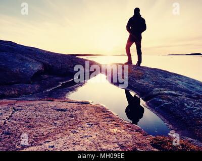 Silhouette of man en vêtements de plein air sur la falaise rocheuse au-dessus de la mer. Hikerthinking pendant le coucher du soleil en arrière-plan. Vous voyagez loin concept. Banque D'Images