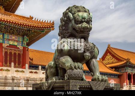 Lion mâle Bronze gardant la porte de l'harmonie suprême. Une patte repose sur un globe symbolisant le pouvoir impérial dans le monde entier. La Cité Interdite, Beijing. Banque D'Images