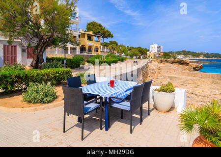 Table de restaurant sur mer dans petit village près de Cala Ratjada, l'île de Majorque, Espagne Banque D'Images