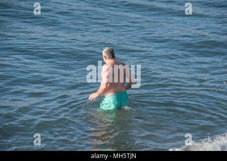 Penzance, Cornwall, UK. 30 avril 2018. Météo britannique. Malgré la forte brise, l'homme a décidé qu'il était assez chaud au soleil d'un matin tôt plonger dans la mer à Penzance, tôt ce matin. Crédit: Simon Maycock/Alamy Live News Banque D'Images