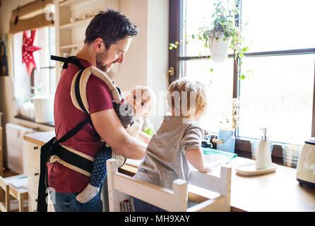 Le père et les deux enfants jusqu'à laver la vaisselle. Banque D'Images
