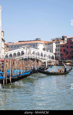 Gondoles devant le pont du Rialto, sur le Grand Canal, Venise, Vénétie, Italie avec un golndolier retourner son bateau jusqu'à son amarrage et les touristes sur la Banque D'Images