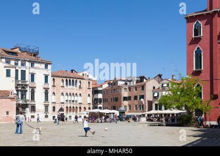 Jeune garçon botter un ballon dans Campo Sant'Anzolo, San Marco, Venise, Vénétie, Italie. La vie quotidienne de Venise. Banque D'Images