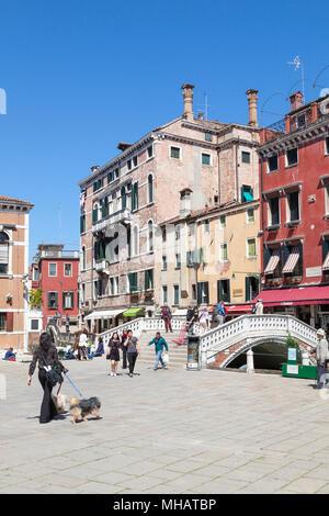 Bâtiments colorés et pont sur le Campo dei Frari, San Polo, Venise, Vénétie, Italie avec une femme locale promener son chien et les touristes Banque D'Images