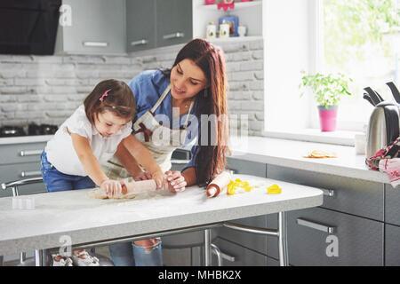 Famille heureuse dans la cuisine. Maison de vacances concept alimentaire. Mère et fille la préparation de la pâte, faire cuire des biscuits. Famille heureuse de faire des cookies à la maison. Cuisine maison et Little Helper Banque D'Images