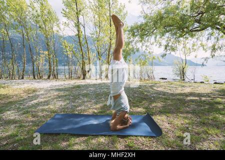 Young woman exercising yoga par le lac et les montagnes, tourné dans le Canton du Tessin, Suisse, Europe. Les gens bien-être détente concept Banque D'Images