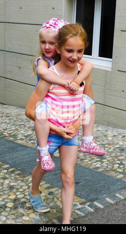 Donner aux enfants, de ferroutage ferroutage transport enfant soeur sur son dos, s'amuser en famille Banque D'Images