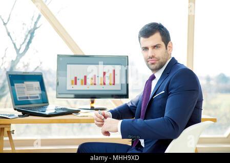 Portrait of young businessman wearing assistant financier suit alors qu'il était assis au bureau et de travailler sur le rapport financier. Banque D'Images