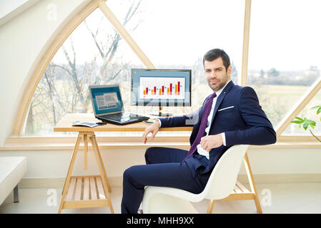 Portrait of confident financial investment businessman sitting in front of laptop tout en travaillant sur le rapport financier. Banque D'Images