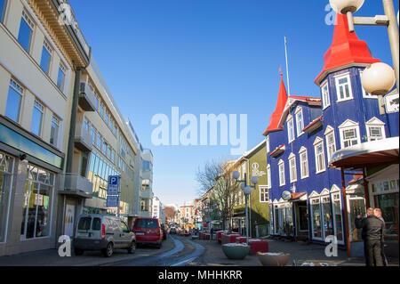 Bâtiments colorés dans la rue principale, le centre-ville d'Akureyri, Islande. Les personnes et véhicules stationnés dans la rue piétonne Hafnarstraeti Banque D'Images