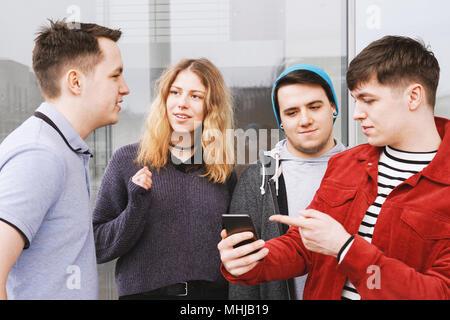 Groupe d'amis adolescents ayant une conversation ou discussion, jeune homme se montrant quelque chose sur son smartphone Banque D'Images
