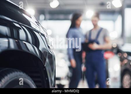 Belle jeune femme parle à beau mécanicien de voiture alors que réparer une voiture en concession Banque D'Images
