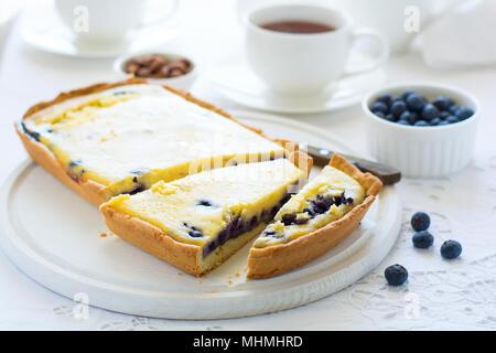 L'heure du thé. Blueberry Cheesecake maison, tasses de thé, les noix et berry sur nappe blanche Banque D'Images