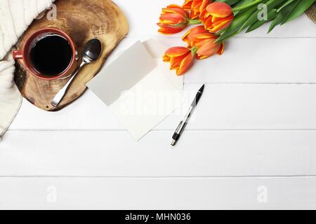 Passage tiré d'un bouquet de fleurs tulipe jaune et orange avec du café noir, avec copie de carte vide de l'espace, et d'un confortable knit throw blanket over white woo Banque D'Images