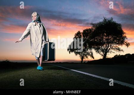 Jeune femme avec valise par la route au coucher du soleil, le style rétro (années 1950, 1960) Banque D'Images