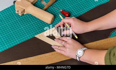 Tanner établit avec l'aide de lignes en morceau de cuir. Sur la table se trouve alène. Processus de travail en atelier Banque D'Images