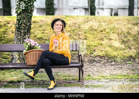 Jeune femme avec des fleurs dans un panier sous le soleil de printemps la ville. Banque D'Images