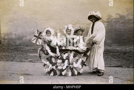 Un homme habillé comme une femme poussant un landau ornés de banderoles et drapeaux et contenant trois enfants dans les bonnets et chapeaux de paille fleurie. Peut-être même d'une robe de l'entrée pour une fête, un défilé ou un événement spécial (ou la Journée de l'Empire couronnement 1911 peut-être?). Date: c.1910 Banque D'Images