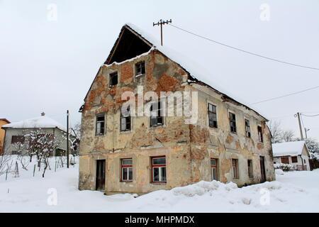 Vieille maison en ruine abandonnée avec des fenêtres cassées, des briques de façade et diminué les murs, couverts dans la neige profonde à côté de route pavée sur froide journée d'hiver Banque D'Images