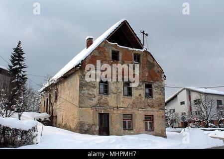 Vieille maison en ruine abandonnée avec des fenêtres cassées, des briques de façade et diminué les murs, couverts dans la neige profonde à côté de route pavée et moderne maison de banlieue Banque D'Images