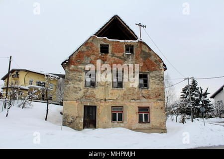 Vieille maison en ruine abandonnée avec des fenêtres cassées, des briques de façade et diminué les murs, couverts dans la neige profonde à côté de route pavée et avec de banlieue moderne Banque D'Images