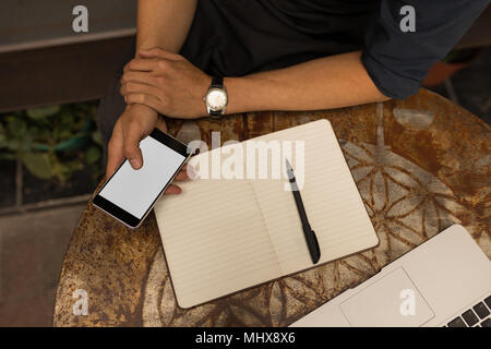 Businessman using mobile phone in cafe