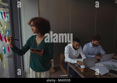 Female Architect with digital tablet écrit le post-it alors que collègues using laptop Banque D'Images