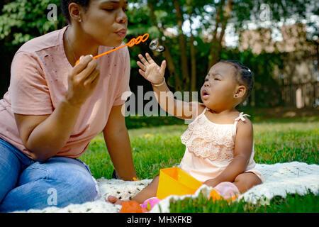 Mid adult woman blowing bubbles in garden pour bébé fille Banque D'Images