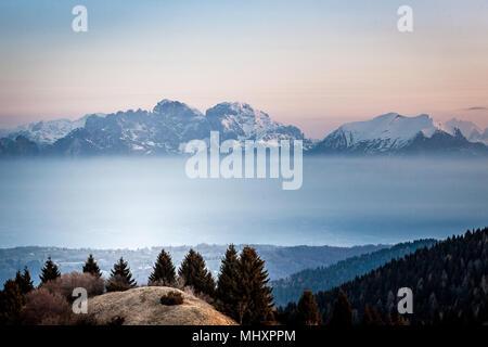 Lever du soleil sur la neige a couvert la dolomite peaks qui émergent de la brume, Padova, Veneto, Italie Banque D'Images