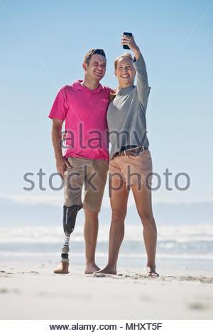 Homme avec jambe artificielle posant pour partenaire féminine avec Selfies lors d'été plage Locations en Afrique du Sud Banque D'Images