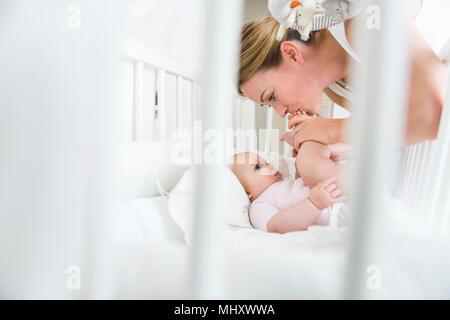 Mère embrassant bébé pieds de lit bébé Banque D'Images