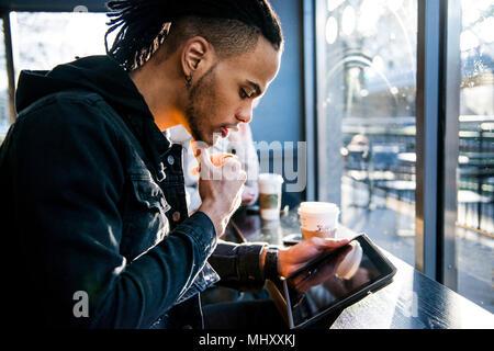 Jeune homme assis dans un café, looking at digital tablet, London, England, UK Banque D'Images